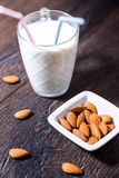 Cup of almond milk with drinking straws and nuts on table Royalty Free Stock Photos