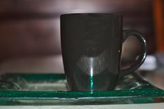Cup on antique plate. Black cup on antique green plate royalty free stock photos