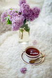 Cup of aromatic black tea with lilac branch Stock Photos
