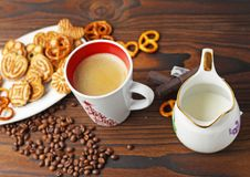 A cup of coffee, grains of coffee and cookies on a wooden table. stock image