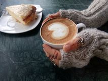 Cup of art coffee latte in girl hands and cake royalty free stock image