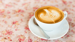 Cup of art latte or cappuccino coffee with retro filter effect a Royalty Free Stock Image