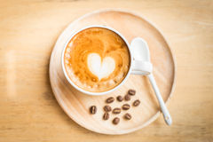 A cup of art latte coffee with coffee beans on the wood table Royalty Free Stock Photos