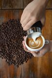 cup of coffee latte art making by barista on old wooden background. stock images