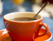 Cup of assam tea with a spoon on a table with blurred background Stock Image