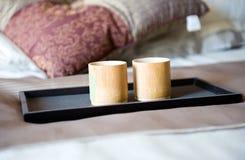 Cup auf einem Bett stockfotografie