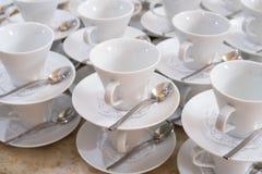 Cup auf Saucers mit Teelöffeln Stockfotos