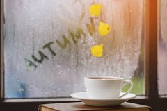 Cup of autumn tea, coffee, chocolate and yellow leaves on rainy window, copy space. Hot drink for autumn mood. Hygge concept royalty free stock photos