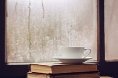 Cup of autumn tea, coffee, chocolate and yellow leaves on rainy window, copy space. Hot drink for autumn mood. Hygge concept stock photo