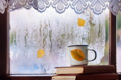 Cup of autumn tea, coffee, chocolate and yellow leaves on rainy window, copy space. Hot drink for autumn mood. Hygge concept. Cup of autumn tea, coffee stock image