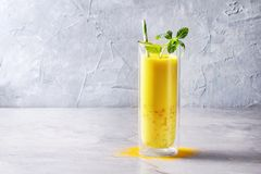 Turmeric golden milk iced latte. Cup of ayurvedic drink golden coconut milk turmeric iced latte with curcuma powder, crushed ice, mint over grey kitchen table stock images