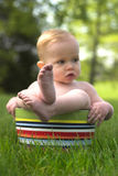 A Cup of Baby. Image of an adorable baby sitting in a colorful, over-sized teacup in the grass Royalty Free Stock Image