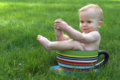 A Cup of Baby. Image of an adorable baby sitting in a colorful, over-sized teacup in the grass Stock Images