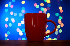 Cup on the background of Christmas lights. Cup with coffee on background of Christmas lights on blue background royalty free stock image