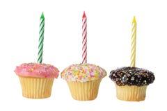 Cup backt mit Geburtstag-Kerzen zusammen Stockbilder