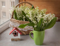 Cup and basket with lilies of the valley  on o the window Royalty Free Stock Images