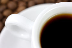 Cup with beverage and coffee beans Stock Photos