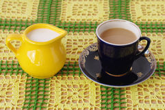 Cup of beverage and jug with milk. Crockery on knitted cloth. cup of beverage and jug with milk Stock Photography