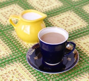 Cup of beverage. jug with milk on back plane. Crockery on knitted cloth. cup of beverage. jug with milk  on back plane Royalty Free Stock Images