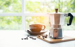 Cup and Bid silver coffee pot on Desktop. In coffee shop stock image