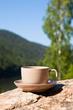 Cup on big stone over nature background Royalty Free Stock Image