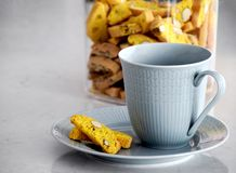 Cup and biscotti. Light blue cup and plate and some biscotti taken from the biscotti jar in the background stock photo
