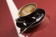 Cup of black coffe. Cup of espresso coffee on the red table Royalty Free Stock Photography
