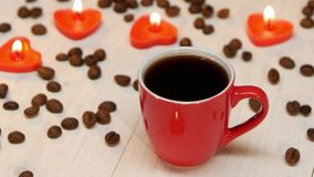 Cup of black coffee on a background of candles. Red small cup of black coffee by candlelight made for a loved one, on the white wooden table lit candles in the stock footage