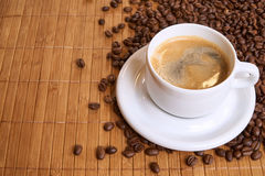 A cup of black coffee on bamboo surrounded by coffee beans with copyspace Stock Image