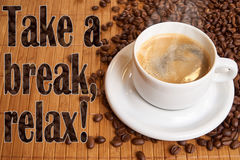 A cup of black coffee on bamboo surrounded by coffee beans - with the text: take a break, relax. A cup of black coffee, surrounded by coffee beans and the Stock Image