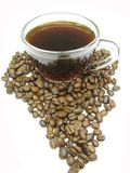 Cup of black coffee among beans africa shape Royalty Free Stock Image