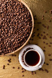 Cup of black coffee and  beans on a golden background Stock Images