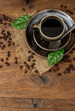Cup of black coffee with beans and green leaves Royalty Free Stock Photos