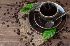 Cup of black coffee with beans and leaves Stock Image