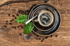 Cup of black coffee with beans and leaves on wooden table Stock Photo