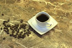 A cup of black coffee and coffee beans lie on a marble table. Close-up royalty free stock images