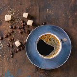 Cup of black coffee. Blue ceramic cup of black hot coffee on saucer, served with brown sugar cubes and coffee beans over old wooden textured background. Top view Royalty Free Stock Photography