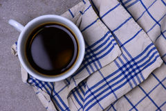 A cup of black coffee on a blue white table cloth Stock Photos