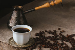 Cup of black coffee, brewing pot and coffee beans Stock Photos