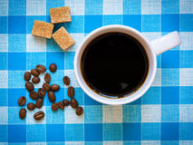 A cup of black coffee, brown sugar cubes and coffee beans Royalty Free Stock Photos