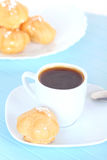 Cup of black coffee and cakes on blue mat Stock Images