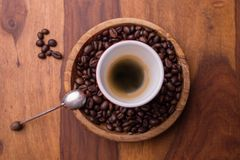 A cup of black coffee in the center of coffee beans with a spoon royalty free stock photography