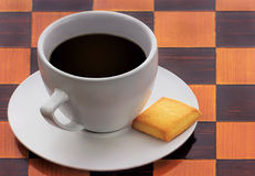 Cup of black coffee on checkerboard background. Cup of black coffee with biscuit on checkerboard background Stock Photography