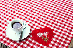 A cup of black coffee on a checkered tablecloth textile. Royalty Free Stock Photos