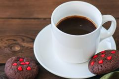 A cup of black coffee and chocolate cookies on a wooden backdrop Stock Photo