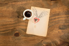 Cup of black coffee with coffee beans heart with wings drawn in pencil. Royalty Free Stock Photography