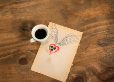 Cup of black coffee with coffee beans heart with wings drawn in pencil. Royalty Free Stock Image