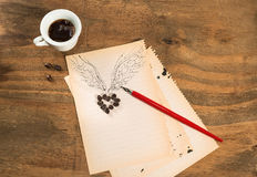 Cup of black coffee with coffee beans heart with wings drawn in pencil and red pen on a blank sheet Stock Photography