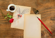 Cup of black coffee with coffee beans heart with wings drawn in pencil and red rose . Royalty Free Stock Photo