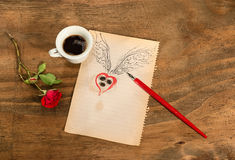 Cup of black coffee with coffee beans heart with wings drawn in pencil and red rose . Stock Images
